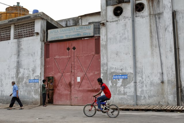 In this Thursday, March 2, 2017 photo, a Bangladeshi man rides past a bicycle in front of the main entrance of the Apex tannery at the highly polluted Hazaribagh tannery area in Dhaka, Bangladesh. (Photo by A.M. Ahad/AP Photo)