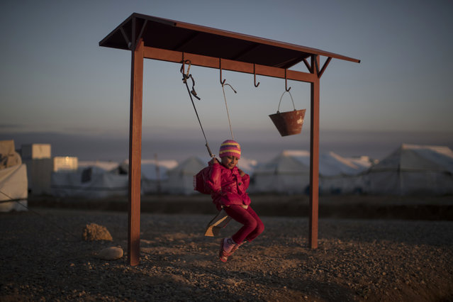A displaced Iraqi girl, who fled fighting between Iraqi security forces and Islamic State militants, balances on a swing at the Hassan Sham camp, east of Mosul, Iraq, Tuesday, March 21, 2017. (Photo by Felipe Dana/AP Photo)