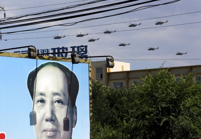 Military helicopters fly in formation above a billboard with a picture of China's late Chairman Mao Zedong during a training session for the upcoming parade marking the 70th anniversary of the end of World War Two, on the outskirts of Beijing, July 2, 2015. (Photo by Jason Lee/Reuters)