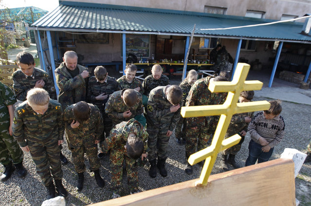 Students from the General Yermolov Cadet School cross themselves in front of an Orthodox crucifix during a two-day field exercise near the village of Sengileyevskoye, just outside the south Russian city of Stavropol, April 13, 2014. (Photo by Eduard Korniyenko/Reuters)