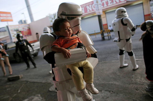 A member of the Star Wars fan club, dressed as a Stormtrooper, poses for a photo with a girl outside a hospital's emergency ward during Star Wars Day celebrations in Monterrey, Mexico May 4, 2016. (Photo by Daniel Becerril/Reuters)