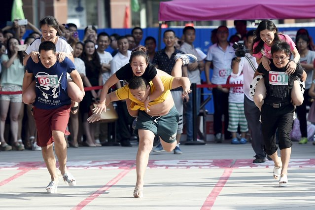 A couple fall as they take part in a high-heels race in Taiyuan, Shanxi province, China, July 3, 2015. The winning couple won a diamond ring after the 50 meter race, according to local media. (Photo by Reuters/Stringer)