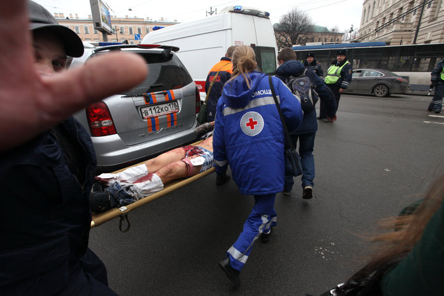Paramedics carrie a subway blast victim into an ambulance after explosion at Tekhnologichesky Institut subway station in St.Petersburg, Russia, Monday, April 3, 2017. (Photo by Alexander Tarasenkov/Interpress via AP Photo)