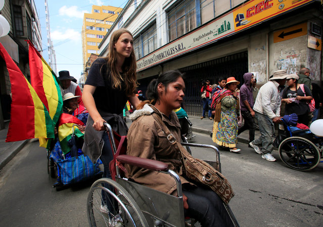 A demonstrator with physical disabilities helped by a volunteer participates in a rally protest calling on the government to provide a monthly subsidy rather than an annual one, in La Paz, Bolivia, May 5, 2016. (Photo by David Mercado/Reuters)