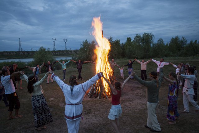 People sing and dance around a campfire during a celebration of the traditional Ivana Kupala (Ivan the Bather) holiday near Omsk, Russia, July 9, 2015. (Photo by Dmitry Feoktistov/Reuters)