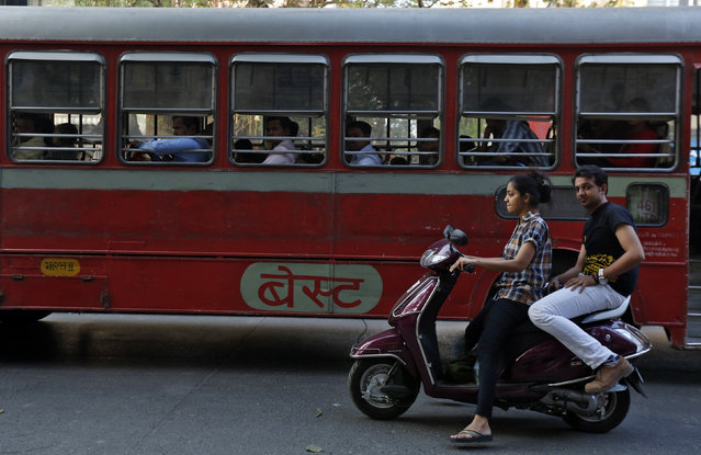 A woman rides a scooter past a passenger bus on a street in Mumbai February 5, 2014. (Photo by Mansi Thapliyal/Reuters)