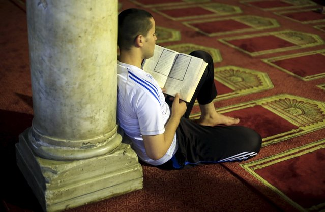 A man reads the Koran after breaking his fast during the holy month of Ramadan at Al-Azhar Mosque in the old Islamic area of Cairo, Egypt, July 9, 2015. (Photo by Amr Abdallah Dalsh/Reuters)