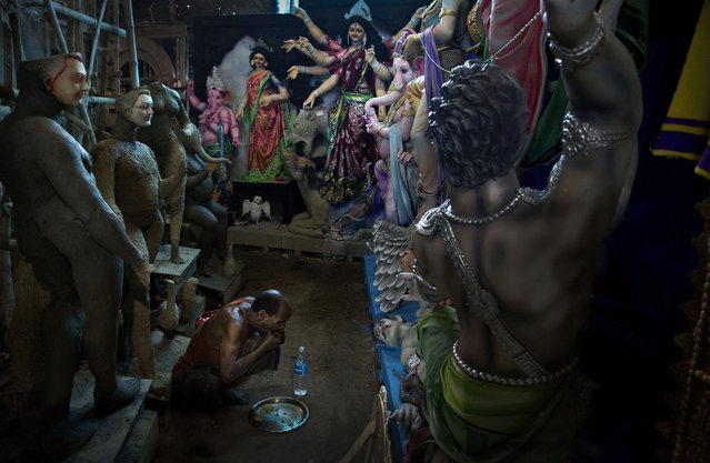 An artisan eats food during a break while working on idols of Hindu goddess Durga inside a workshop in Gauhati, India, Wednesday, September 25, 2019. The idols are being made for worship venues ahead of Durga Puja festival that begins first week of October. (Photo by Anupam Nath/AP Photo)
