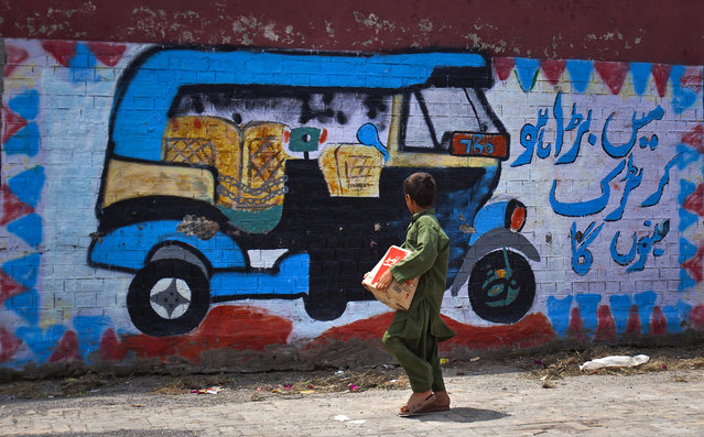 "A Pakistani boy looks a mural of a three-wheeled tuk-tuk that is painted on the wall of a school in Rawalpindi, Pakistan, Monday, July 6, 2015. Writing in Urdu reads, ""when I grow up, I will become a truck"". (Photo by Anjum Naveed/AP Photo)"