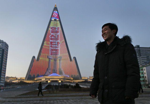 In this December 20, 2018 photo, light designer Kim Yong Il smiles during an interview with the Associated Press as his creation, the light show displaying propaganda messages on the facade of the pyramid-shaped Ryugyong Hotel, is seen in the background in Pyongyang, North Korea. For several hours each night, the building that doesn't have electricity inside becomes the backdrop of a massive light show in which more than 100,000 LEDs flash images of famous statues and monuments, bursts of fireworks, party symbols and political slogans. (Photo by Dita Alangkara/AP Photo)