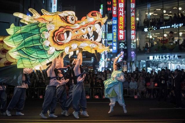 "Participants perform a dragon dance as they march during a lantern parade marking the start of a month- long ""Lotus Lantern Festival"" to celebrate the upcoming Buddha' s birthday, in Seoul on April 29, 2017 Buddha' s birthday falls on May 3. (Photo by Ed Jones/AFP Photo)"