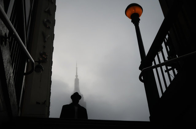 A man walks past a fog shrouded Empire State Building on April 6, 2019, in New York City. (Photo by Gary Hershorn/Getty Images)