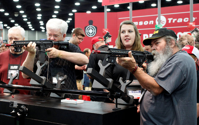 Gun enthusiasts test out laser sights at Crimson Trace Corp. at the National Rifle Association's annual meetings and exhibits show in Louisville, Kentucky, May 21, 2016. (Photo by John Sommers II/Reuters)