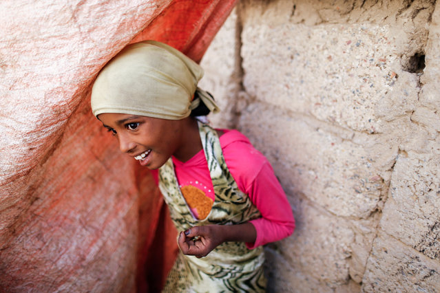 A girl looks from the door of her house during a house-to-house vaccination campaign in Sanaa, Yemen February 20, 2017. (Photo by Khaled Abdullah/Reuters)