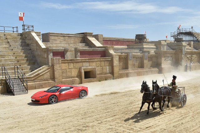 "Ferrari driver Fabio Barone and his Ferrari 458 Italia competes against a Roman chariot drawn by two horses on ""Ben Hur"" movie set at Cinecitta World amusement park on May 11, 2017 in Castel Romano near Rome. (Photo by Andreas Solaro/AFP Photo)"