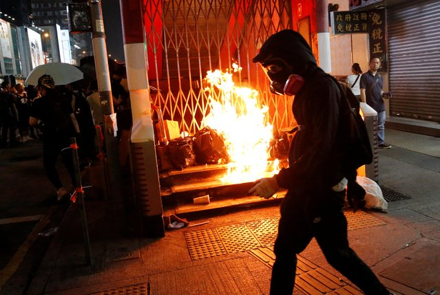 An anti-government protester walks past a burning barrier outside Mong Kok MTR station during a protest in Hong Kong, China on October 27, 2019. (Photo by Tyrone Siu/Reuters)