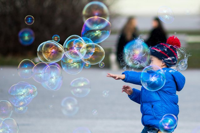 A young boy plays with soap bubbles near Hofburg Palace at Heldenplatz, one of the top tourists attractions in Vienna, Austria, January 26, 2016. (Photo by Christian Bruna/EPA)