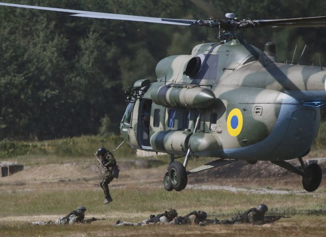 Members of the National Guard of Ukraine jump out a MI-8 helicopter during military tactical exercises at a training base near Kiev, Ukraine, July 22, 2015. (Photo by Valentyn Ogirenko/Reuters)
