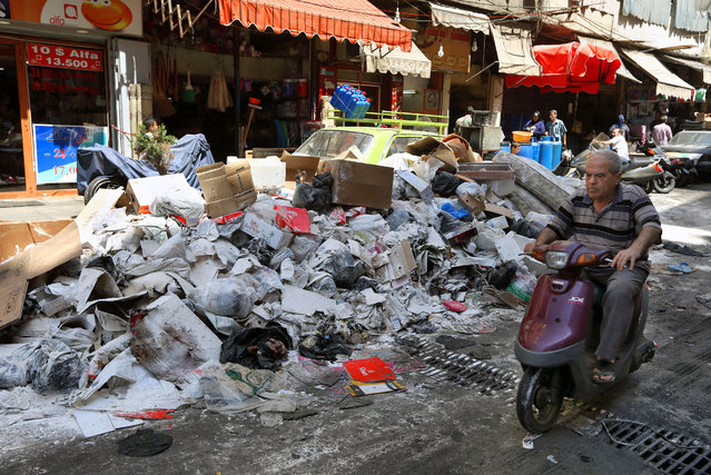 A man rides a motorcycle past a pile of garbage covered with white pesticide in the Palestinian refugee camp of Sabra in Beirut, Lebanon, Thursday, July 23, 2015. (Photo by Bilal Hussein/AP Photo)