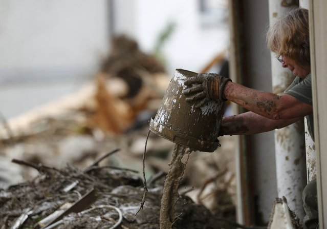 A woman removes dirt from a house after the floods in the town of Braunsbach, Germany, May 30, 2016. (Photo by Kai Pfaffenbach/Reuters)