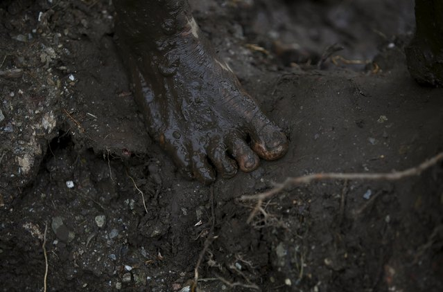 The muddied foot of a Nepalese Army personnel is seen as he searches for the victims at Lumle village in Kaski district July 30, 2015. (Photo by Navesh Chitrakar/Reuters)