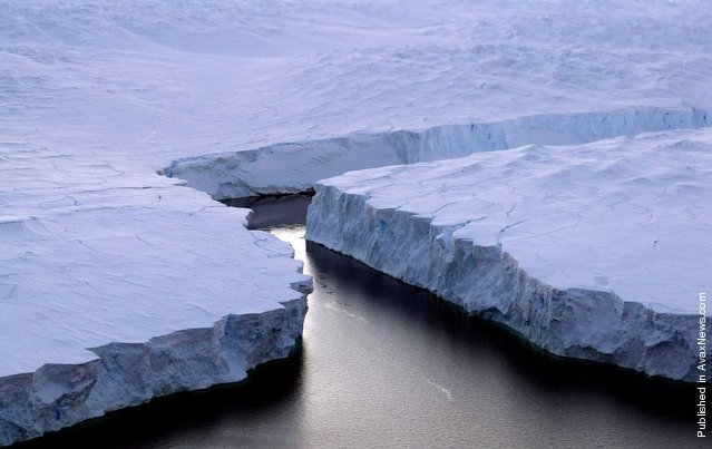 An enormous iceberg, right, breaks off the Knox Coast in the Australian Antarctic Territory