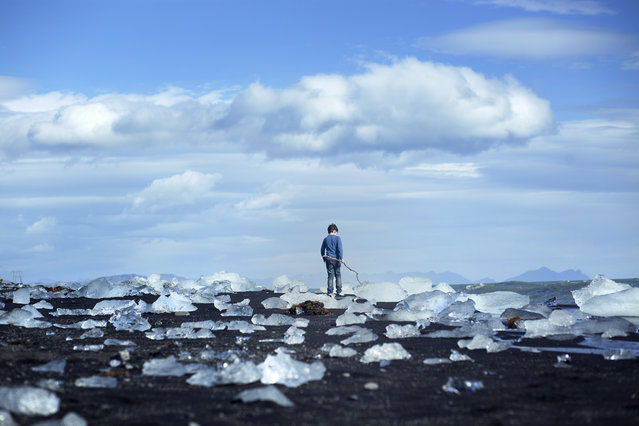 """The Explorer"". In the Freezing cold air of Jökulsárlón, Iceland, A boy ran around, discovering the glistening washed up Ice blocks, remnants of huge icebergs broken up that drifted into the sea. Photo location: Jökulsárlón, Iceland. (Photo and caption by Ronen Goldman/National Geographic Photo Contest)"