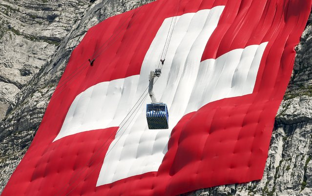 A cablecar descents in front of a huge 80x80 metres (262x262 feet) Swiss national flag on the western face of the north-eastern Swiss landmark Mount Saentis, Switzerland July 31, 2015. (Photo by Arnd Wiegmann/Reuters)