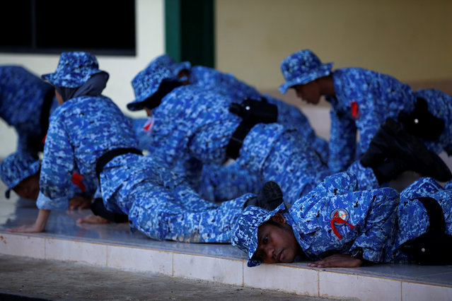 "Participants of the Bela Negara – ""defend the nation"" – programme fall to the ground following a trainer's order at a training centre in Rumpin, Bogor, West Java, Indonesia June 2, 2016. (Photo by Darren Whiteside/Reuters)"
