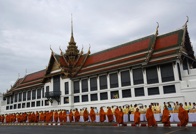 Buddhist monks line up to receive offerings from devotees outside Grand Palace during the 70th anniversary celebrations of Thai King Bhumibol Adulyadej's accession to the throne in Bangkok, Thailand, Thursday, June 9, 2016. (Photo by Sakchai Lalit/AP Photo)