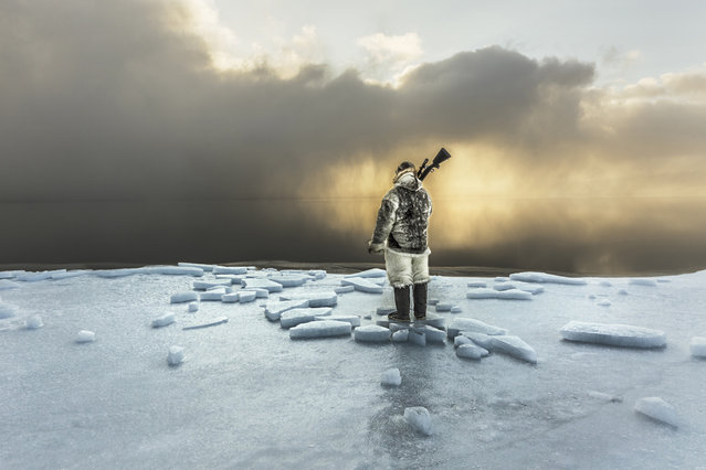 Naimanngitsoq Kristiansen keeps watch at the edge of the sea ice, waiting for harp seals or walrus to come near. Northern Greenland, 2015. (Photo by Cristina Mittermeier)