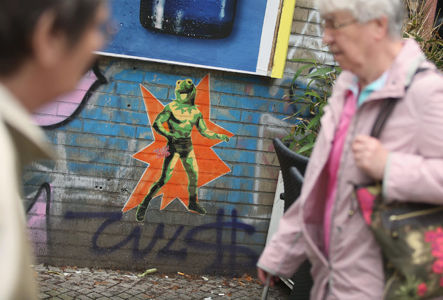 People walk by a street artist's version of Kermit the Frog in Oppelner Strasse in Kreuzberg district on June 26, 2014 in Berlin, Germany. Berlin, with its long tradition of counter-culture, has become a mecca for street art of all dimensions and messages. (Photo by Sean Gallup/Getty Images)