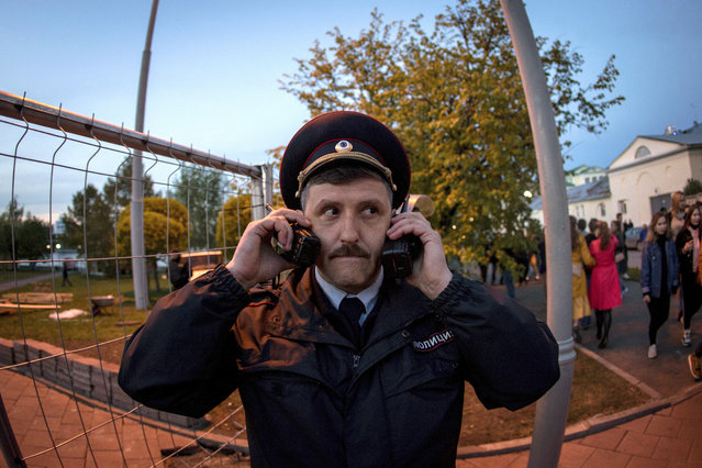 A police officer speaks on two walkie talkies as demonstrators gather in front of a new builded fence blocked by police to protest plans to construct a cathedral in a park in Yekaterinburg, Russia, Wednesday, May 15, 2019. Hundreds of riot police have surrounded a park in Russia's fourth-largest city before what's expected to be a third consecutive day of protests against building a new cathedral. (Photo by Anton Basanayev/AP Photo)