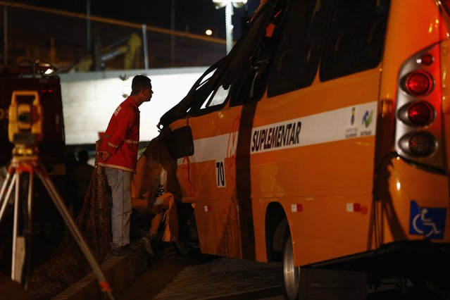 A worker inspects a bus which was trapped underneath a bridge that collapsed while under construction in Belo Horizonte, July 3, 2014. The unfinished overpass collapsed in the Brazilian World Cup host city of Belo Horizonte on Thursday, killing at least one person and casting a shadow over a tournament that has suffered repeated construction accidents and delays. (Photo by Ivan Alvarado/Reuters)