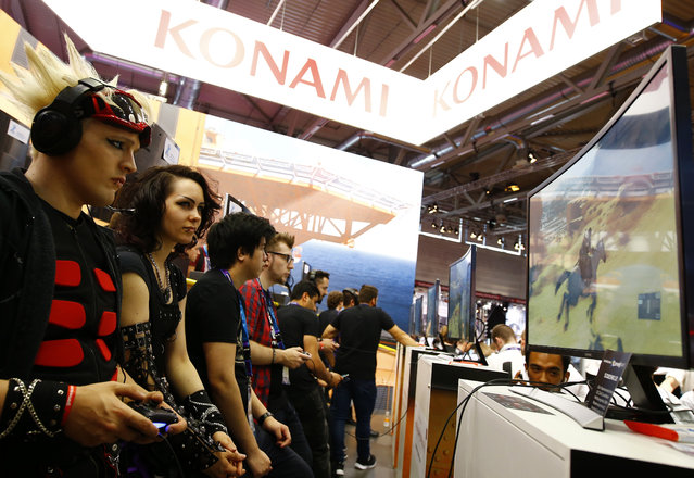 """Gamers play """"Diamond Dogs"""" produced by Konami during the Gamescom 2015 fair in Cologne, Germany August 5, 2015. (Photo by Kai Pfaffenbach/Reuters)"""