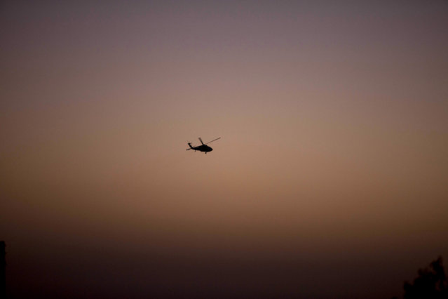 An Israeli military helicopter flies over the village of Halhul, near the West Bank town of Hebron, where the bodies of the three missing Israeli teenagers were found, Monday, June 30, 2014. (Photo by Majdi Mohammed/AP Photo)