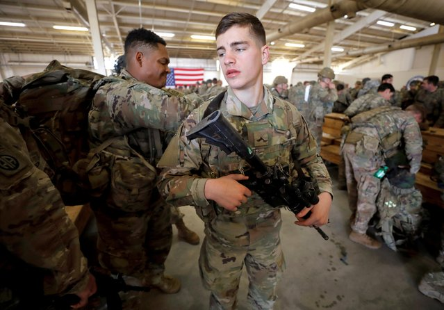 A U.S. Army paratroopers of an immediate reaction force from the 2nd Battalion, 504th Parachute Infantry Regiment, 1st Brigade Combat Team, 82nd Airborne Division, help one another prepare for their departure aboard a C-17 transport aircraft leaving Fort Bragg, North Carolina, U.S. January 1, 2020. (Photo by Jonathan Drake/Reuters)