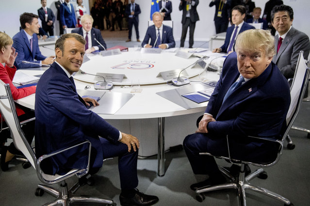 French President Emmanuel Macron, center left, and President Donald Trump, center right, participate in a G-7 Working Session on the Global Economy, Foreign Policy, and Security Affairs the G-7 summit in Biarritz, France, Sunday, August 25, 2019. Also pictured is German Chancellor Angela Merkel, left, Canadian Prime Minister Justin Trudeau, second from left, British Prime Minister Boris Johnson, third from left, President of the European Council Donald Tusk, center, Italian Prime Minister Giuseppe Conte, top second from right, and Japanese Prime Minister Shinzo Abe, right. (Photo by Andrew Harnik/AP Photo/Pool)