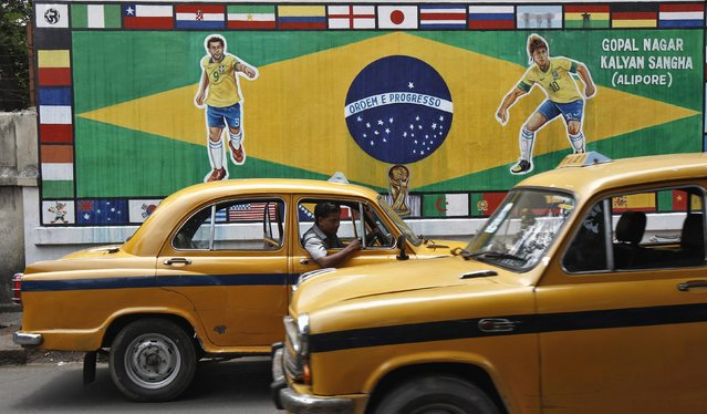 Yellow Ambassador taxis are seen in front of a roadside wall decorated with paintings of Brazilian players Fred and Neymar, a large Brazilian flag and World Cup teams' national flags in Kolkata June 12, 2014. (Photo by Rupak De Chowdhuri/Reuters)