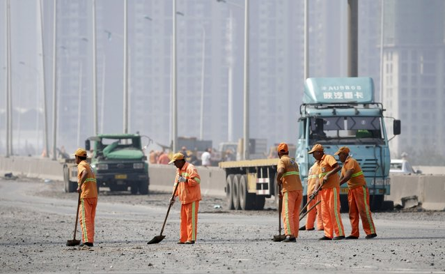 Workers clean debris on a highway near the site of the explosions at the Binhai new district, Tianjin, August 13, 2015. (Photo by Jason Lee/Reuters)
