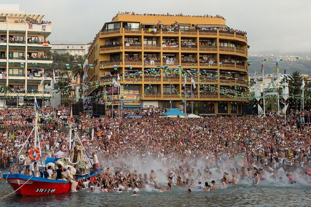 People spread water after carriers of the Great God Power brotherhood have loaded the Virgen del Carmen statue on July 15, 2014 at Puerto de la Cruz dock on the Canary island of Tenerife, Spain. (Photo by Gonzalo Arroyo Moreno/Getty Images)