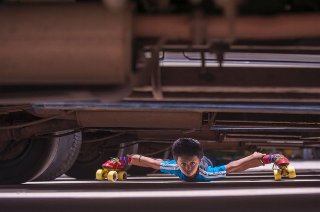 A super flexible schoolboy has become a limbo legend - by roller-skating under 39 cars in a row. It took six-year-old Gagan Satish just 29 seconds to cover a distance of nearly 70 metres with his face just five inches from the ground. (Photo by Arkaprava Ghosh/Barcroft Media India)