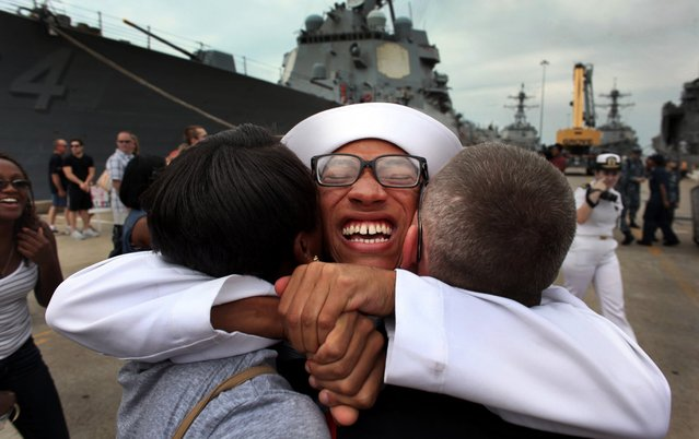 Petty Officer 3rd Class Michael Williams, a Cryptologic Technician Technical from Miami hugs friends and family members on Pier 5 of Norfolk Naval Base, during the homecoming event following a six-month deployment of the Oliver Hazard Perry-class frigate USS Elrod, July 19, 2014, in Norfolk, Va. (Photo by Martin Smith-Rodden/AP Photo/The Virginian-Pilot)