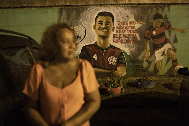 Marilia Barros da Silva stands next to a mural of her late son Arthur Vinicius, one of the victims of the fire at Brazil's Flamengo soccer club training complex, near her house in Volta Redonda, Brazil, Thursday, February 6, 2020, days before the one-year mark since the fire killed 10 academy players and injured three others, all aged between 14 and 16 years-old at the time. (Photo by Leo Correa/AP Photo)