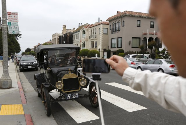 A tourist snaps a photograph of a 1915 Ford Model T after it arrived from Detroit at the Palace of Fine Arts in San Francisco, California August 19, 2015. The 3,500 mile, 34-day road trip recreated the cross country journey made by Edsel Ford 100 years ago, when he arrived at the Palace of Fine Arts for the 1915 World's Fair. (Photo by Robert Galbraith/Reuters)