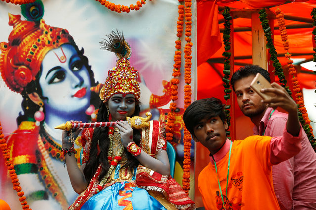 People take selfie with a girl dressed as Lord Krishna during the celebration of Janmashtami festival, which marks the birth anniversary of Lord Krishna, in Dhaka, Bangladesh, August 14, 2017. (Photo by Mohammad Ponir Hossain/Reuters)