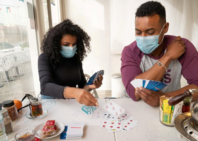 People wear protective face masks, following the outbreak of the new coronavirus, as they play cards in a coffee shop in Salmiya, Kuwait, February 26, 2020. (Photo by Stephanie McGehee/Reuters)