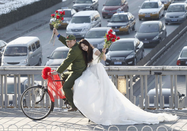 """An engaged couple sits on a bicycle as they pose for wedding photographs to the theme of """"naked wedding"""", on a pedestrian bridge on Valentine's Day in central Beijing February 14, 2011. """"Naked wedding"""" is a popular new expression in China which means young couples get married with no houses, cars or little bank savings. (Photo by Reuters/China Daily)"""