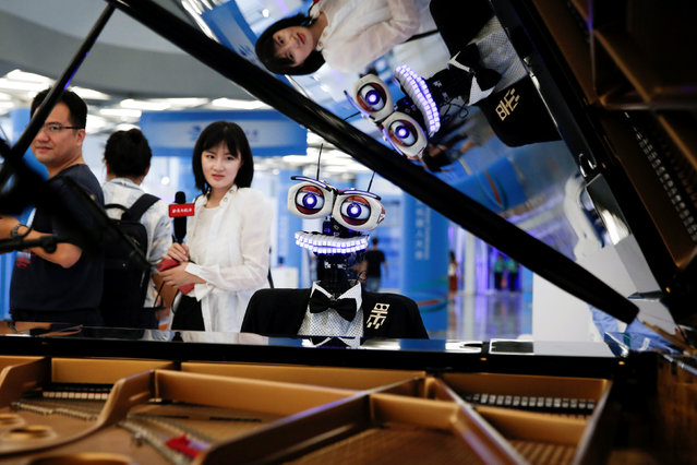 "People watch the robot ""Teo Tronico"", designed by Matteo Suzzi, play piano and sing popular songs at the 2017 World Robot Conference in Beijing, China August 22, 2017. (Photo by Thomas Peter/Reuters)"