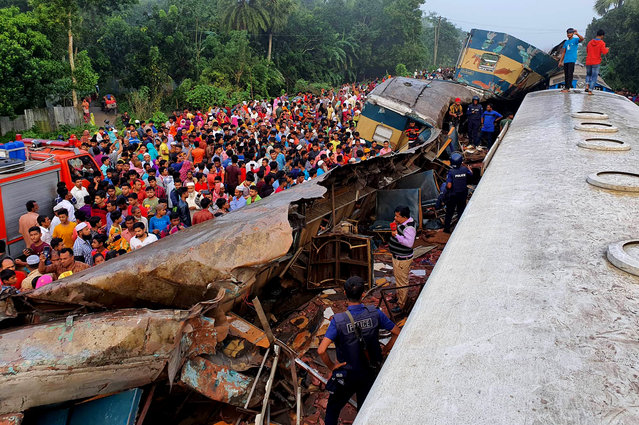 People gather near badly damages coaches after two speeding trains collided in in Brahmanbaria district, 82 kilometers (51 miles) east of the capital, Dhaka, Bangladesh, Tuesday, November 12, 2019. More than a dozen people were killed and scores were injured. (Photo by Xinhua News Agency/Barcroft Media)